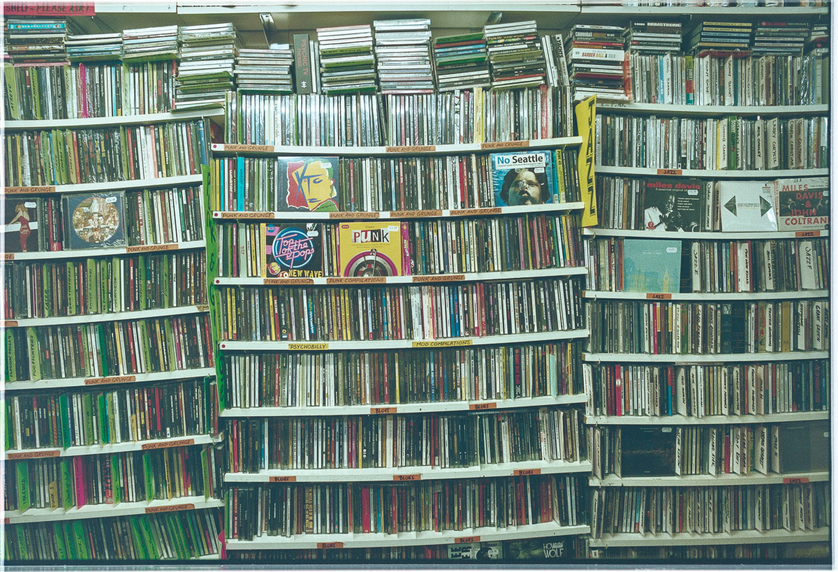A flat-on view of several shelves of CDs which are bending under the weight.