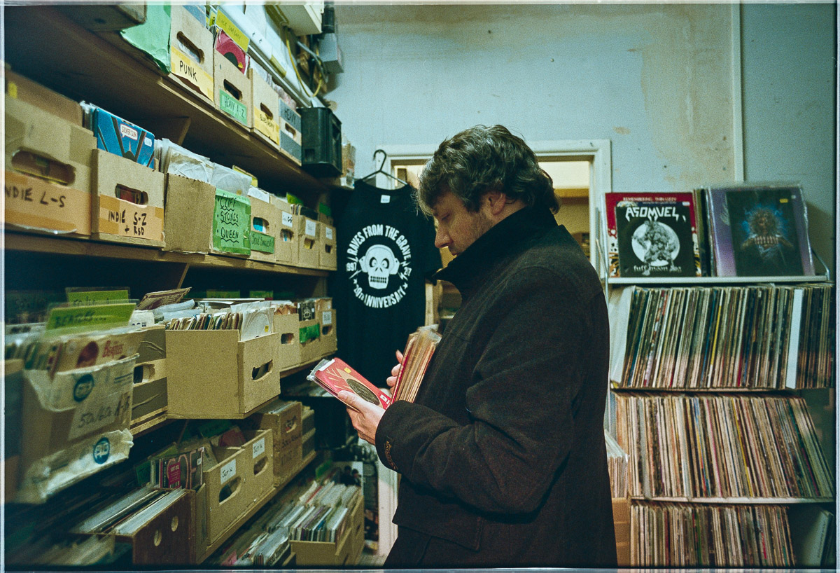 A male customer in a black coat looks through boxes of vinyl 45rpm records.