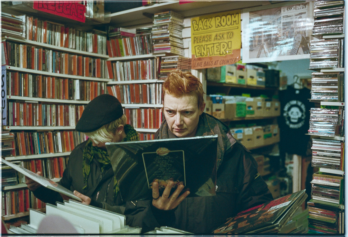 A woman with red hair looks intently at the back of a record sleeve while another woman to her side looks at another.