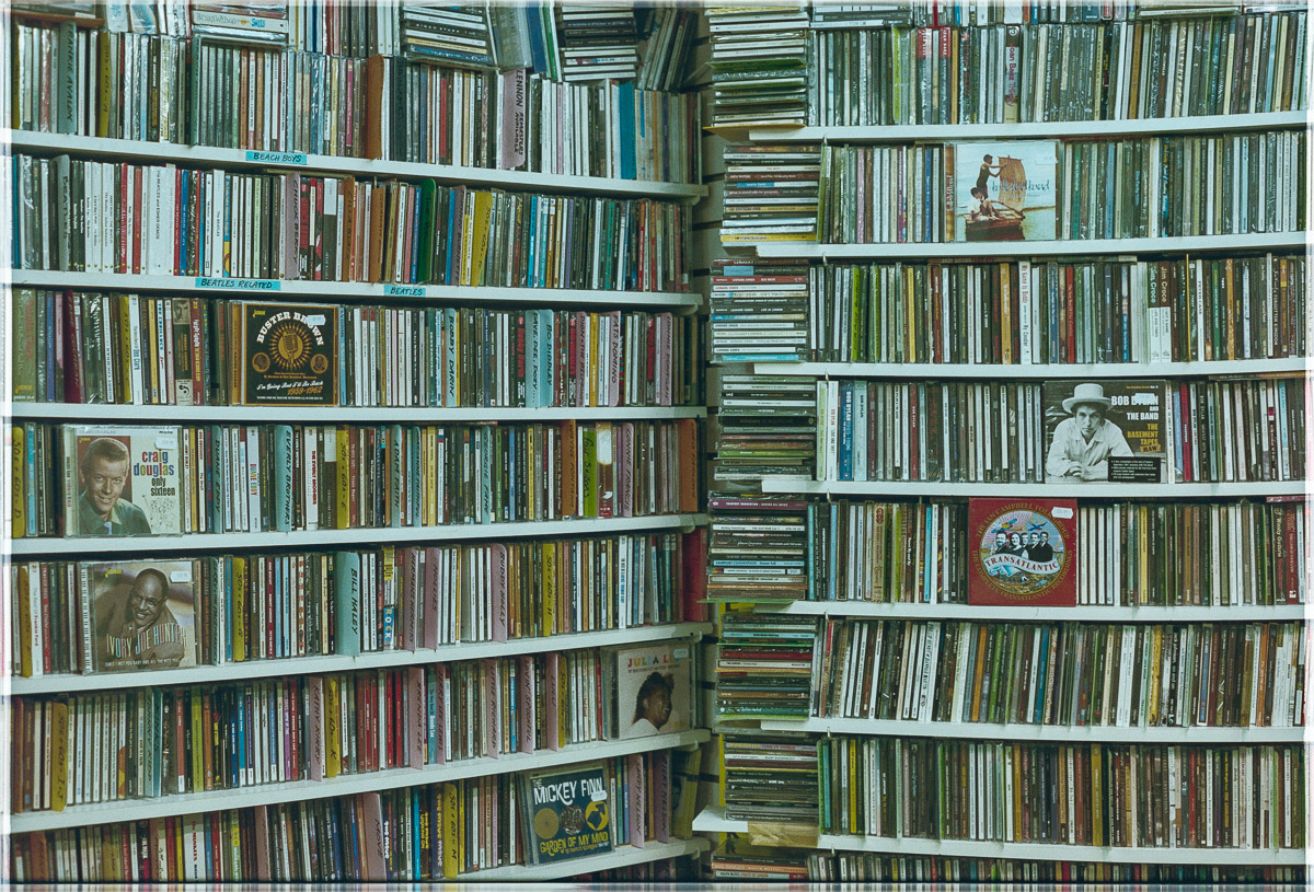 Two walls of CDs join at a floor to ceiling stack of more CDs.