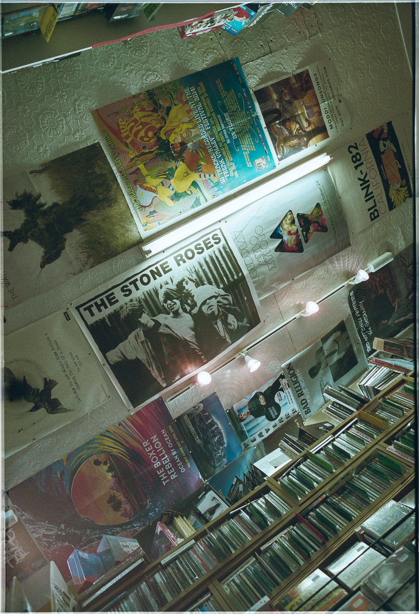 Looking up at the ceiling which has posters pinned to it, The Stone Roses being the central poster in the image.