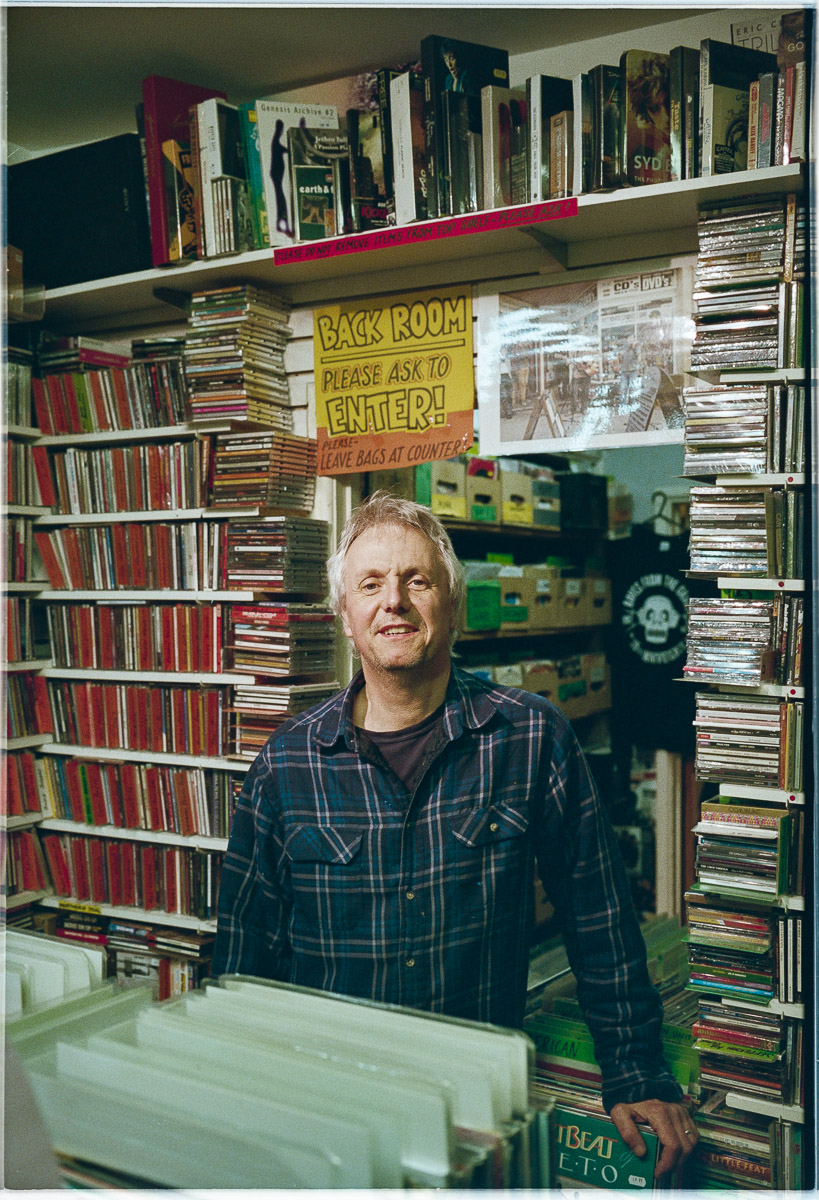Portrait of Richard Churchyard, owner of Raves from the Grave record shop in Frome, with records and CDs visible all around him.