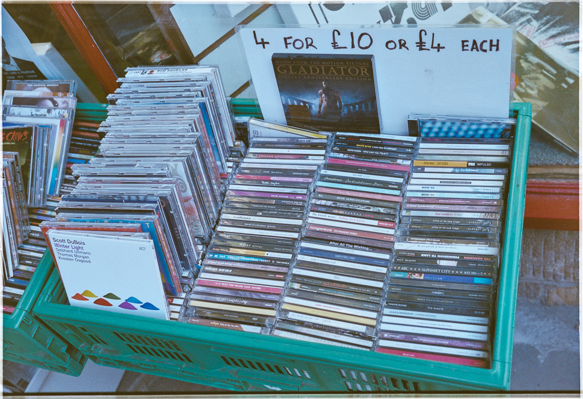 """A box in the shop doorway containing CDs is marked """"4 for £10""""."""
