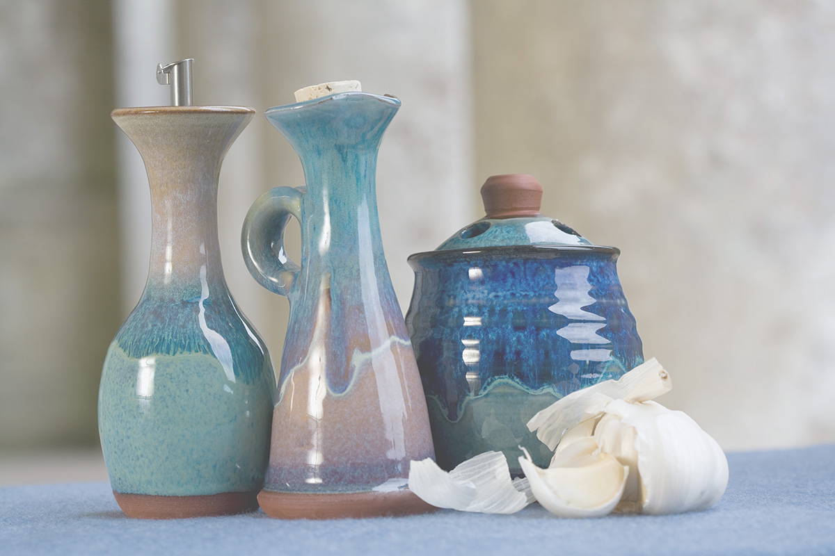 Three ceramic products in a row, an oil bottle, a jug and a garlic roaster, on a blue cloth with broken garlic bulbs lying next to them.