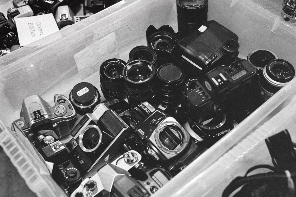 A plastic crate full of old camera bodies and lenses.