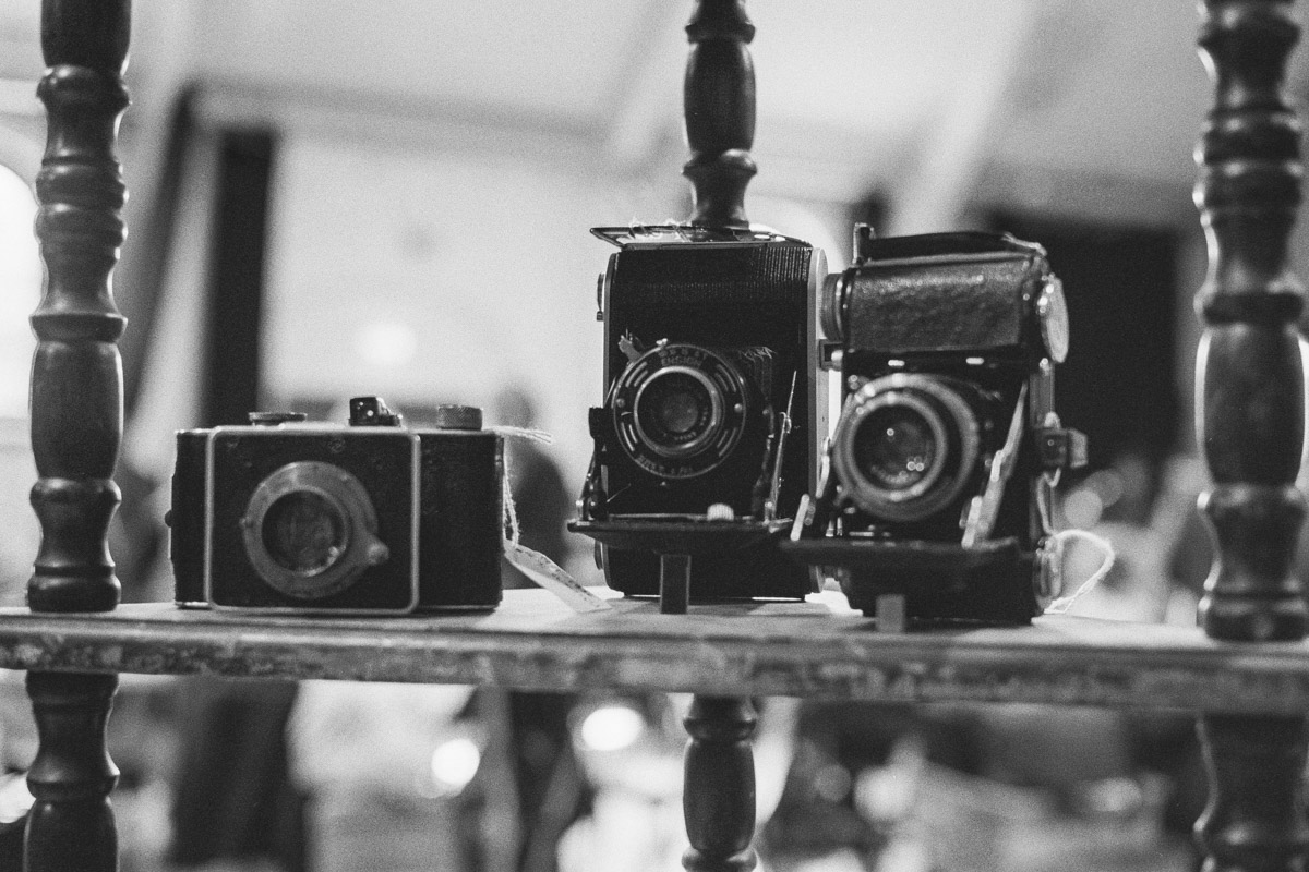 Three early film cameras on a wooden display shelf.