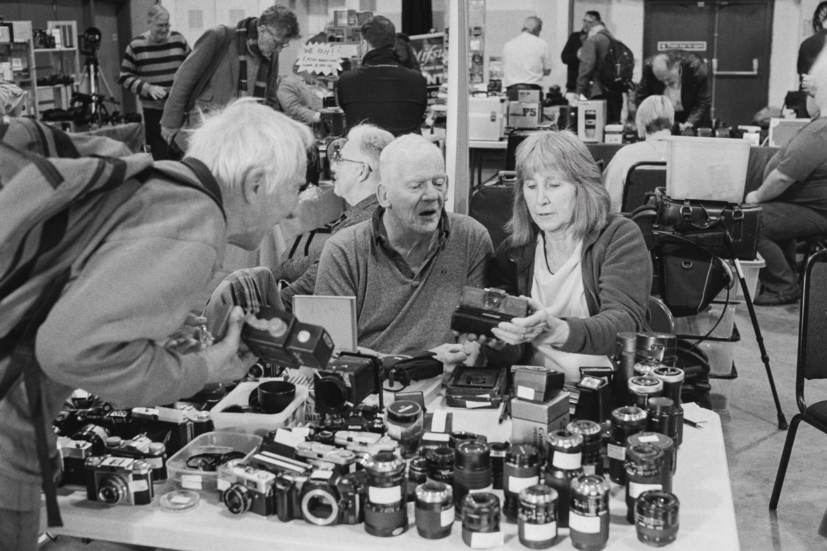 A man and a woman running one of the camera stalls help a male customer looking at a Polaroid camera.