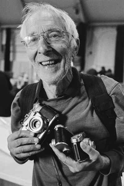 A man holds three very old cameras he's just bought.