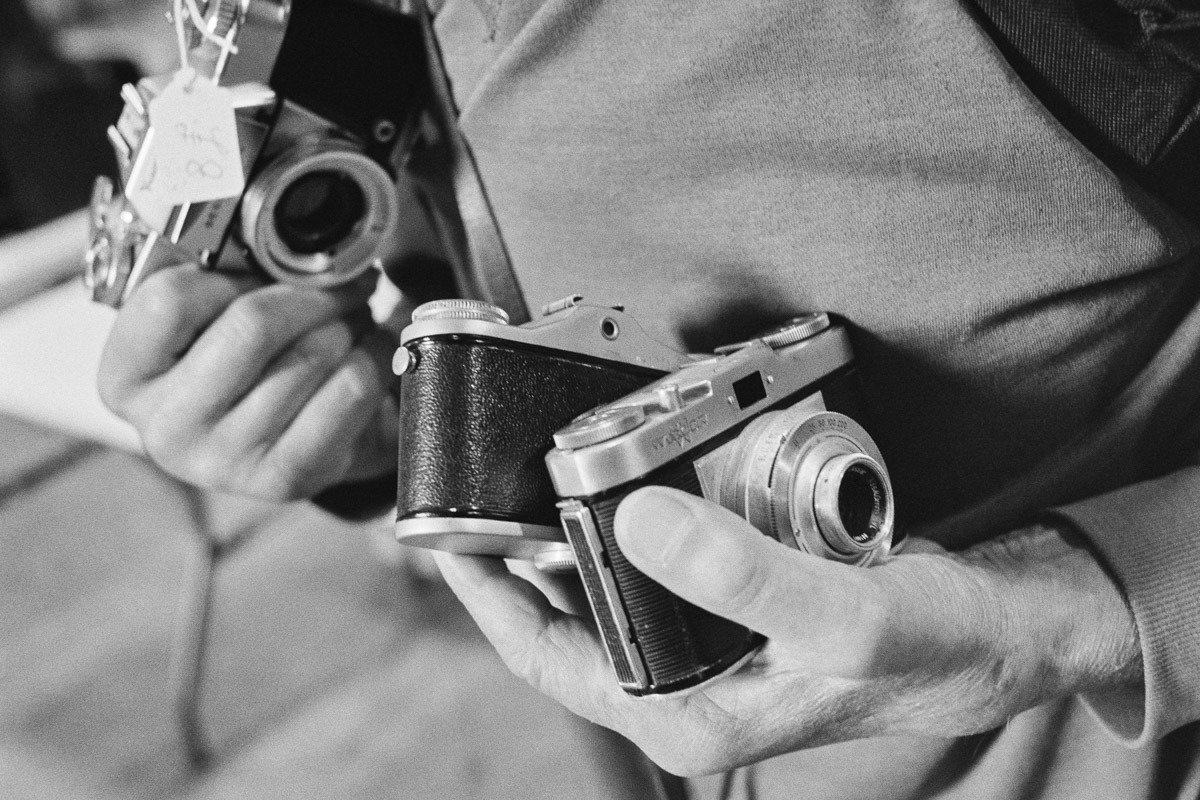 Close-up of a man's hands holding three cameras.
