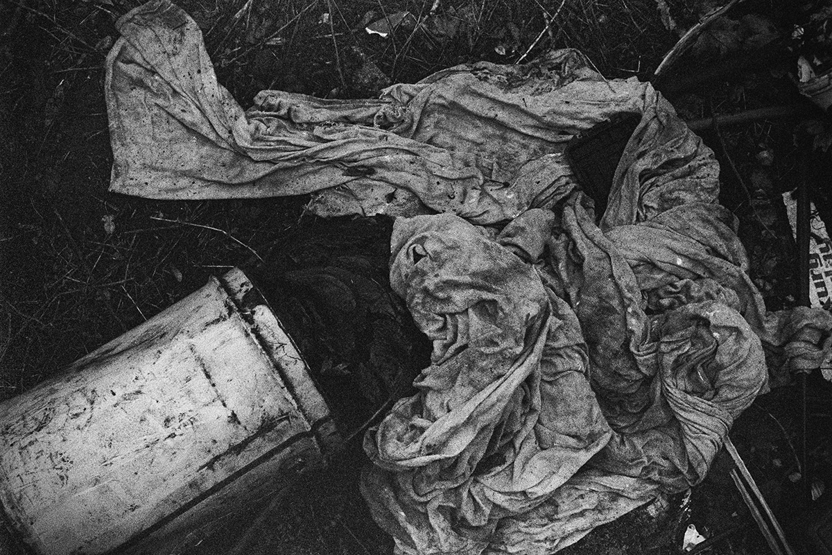 Black and white view of an upturned large metal can with dirty rags strewn nearby.