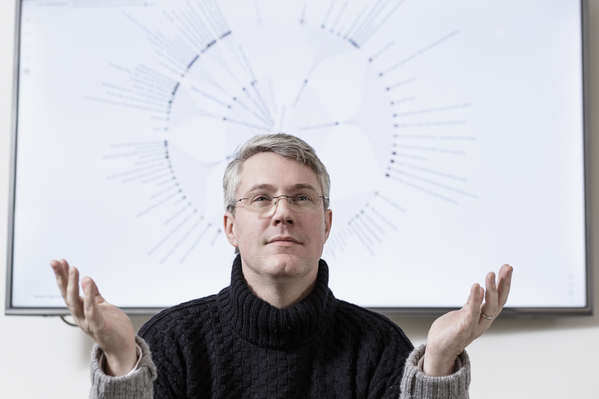 Liam McGee poses with his hands raised, palms-up in a supplicant pose, with a data graph mimicking a halo behind his head.