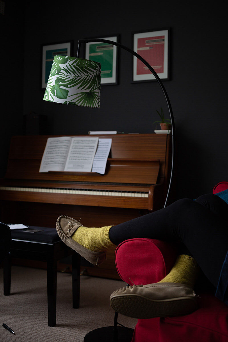 A piano in the background with someone's feet in the foreground, wearing yellow socks and resting on the red arm of a comfy chair. I green leaf-pattern lamp hangs above.