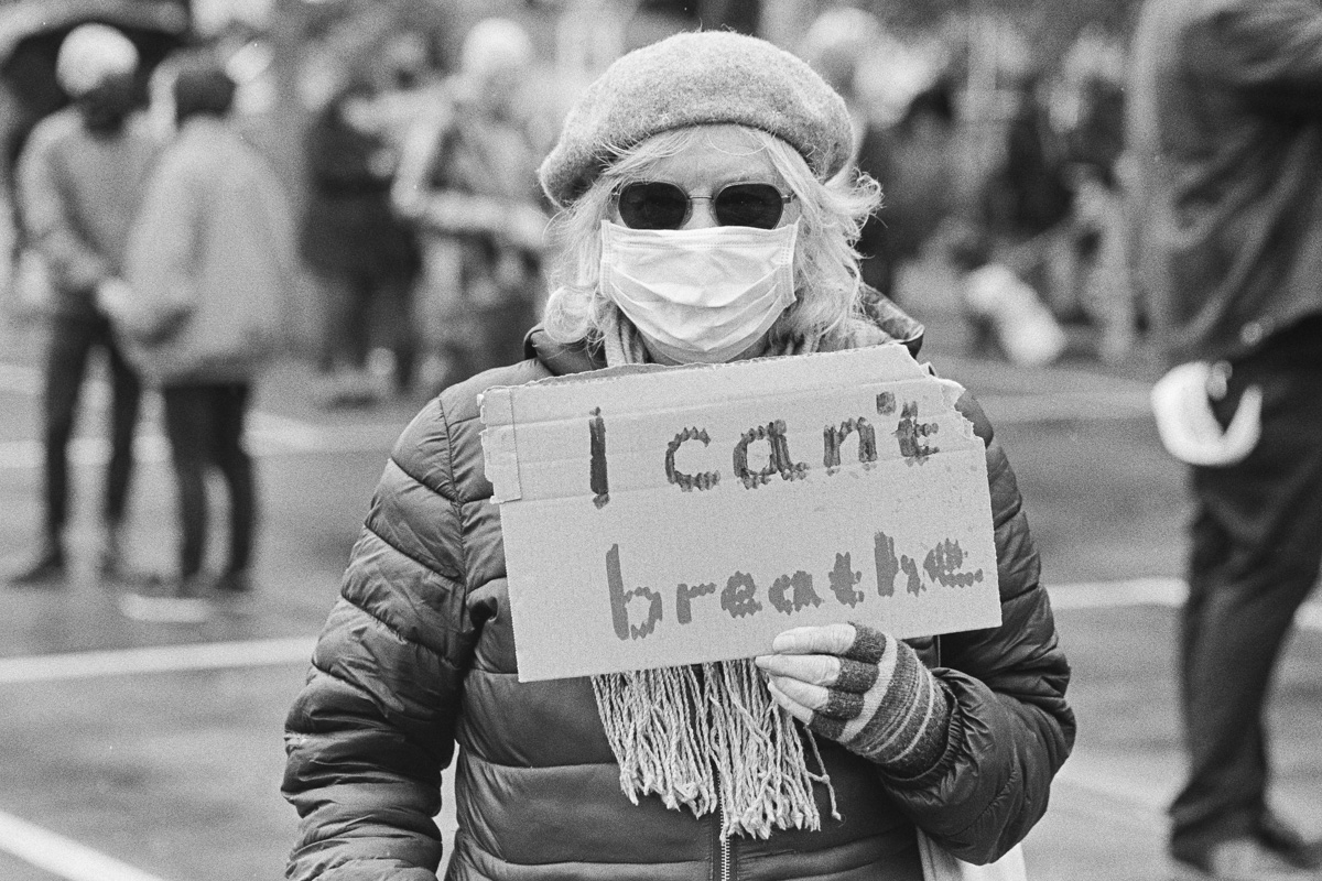 """An older female protestor carries a piece of cardboard on which is written, """"I can't breathe"""""""