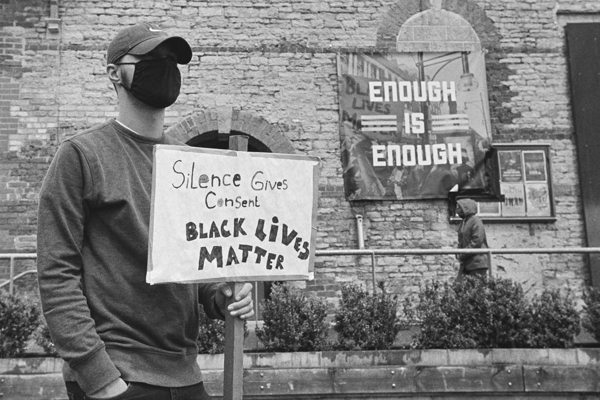 """A male protester wearing a black mask carries a placard which reads """"Silence gives consent. Black lives matter"""". A banner on the building behind him reads """"Enough is enough."""""""