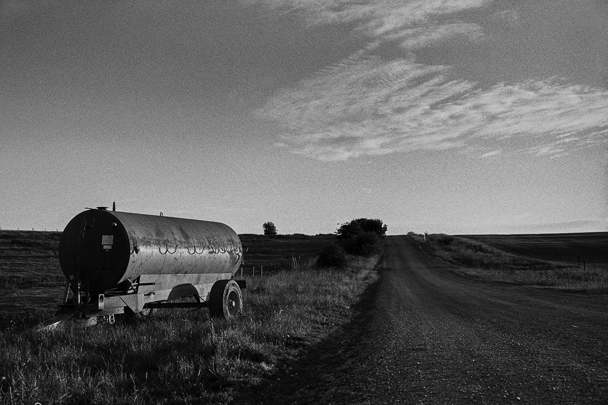Black and white photo of a farm tanker parked on the edge of a field with a mettled track leading past and to the horizon on a sunny evening.
