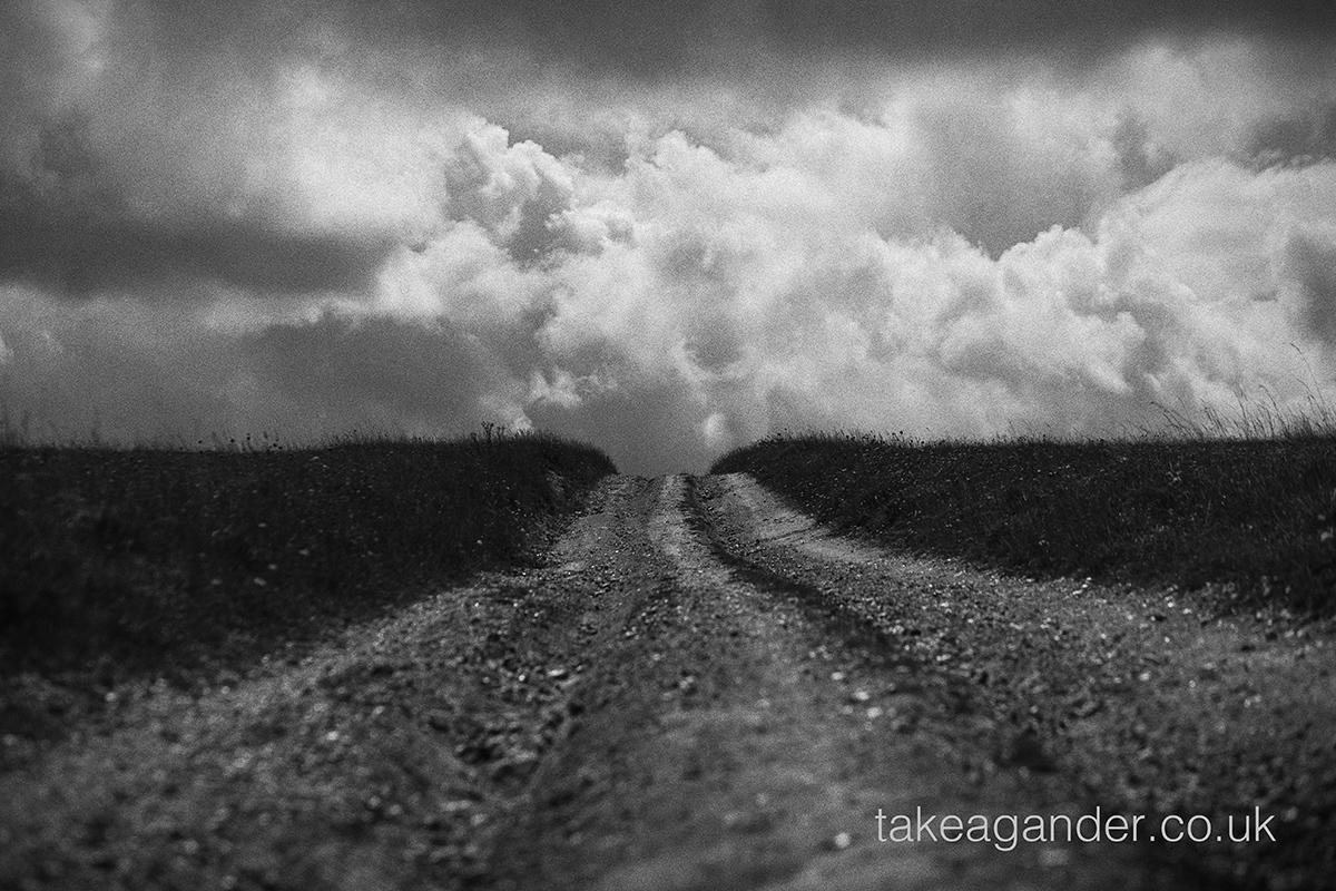 Moody black and white landscape of a chalk track leading to the near horizon on Salisbury Plain