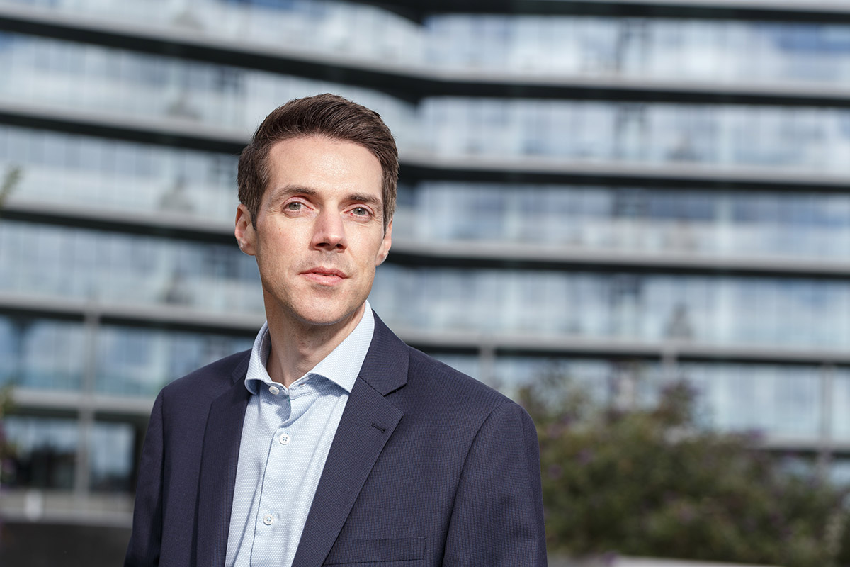 Portrait of a male business man looking to camera with the strong horizontal lines of an office block blurred behind him.