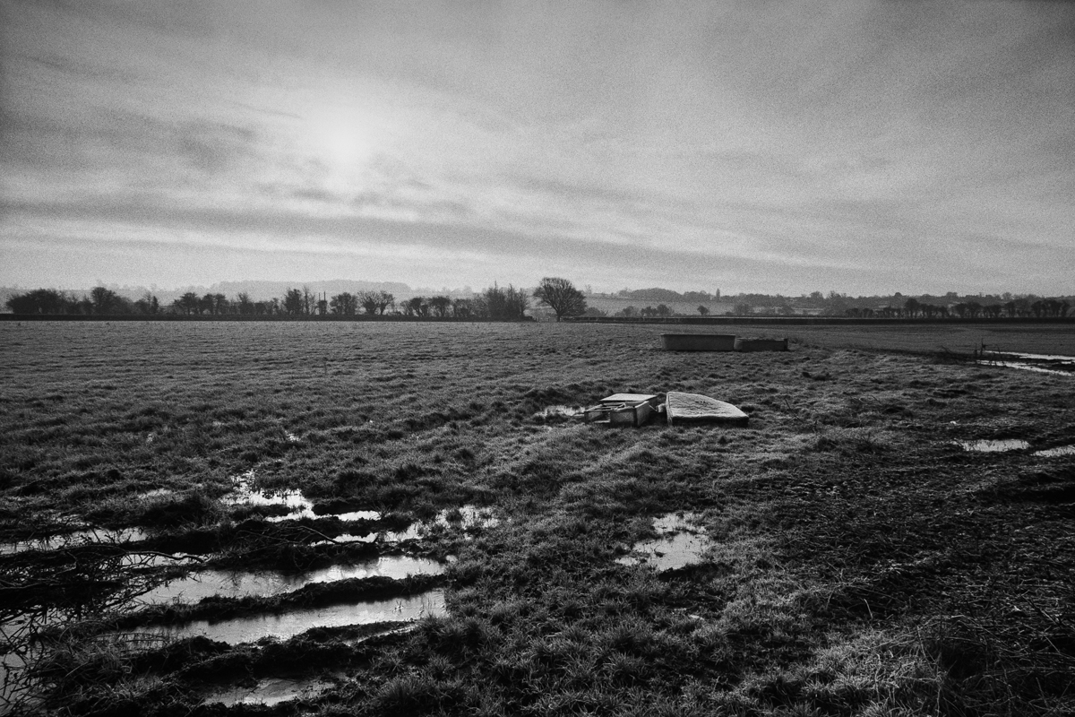 Black and white landscape of a waterlogged field with a dumped bed.