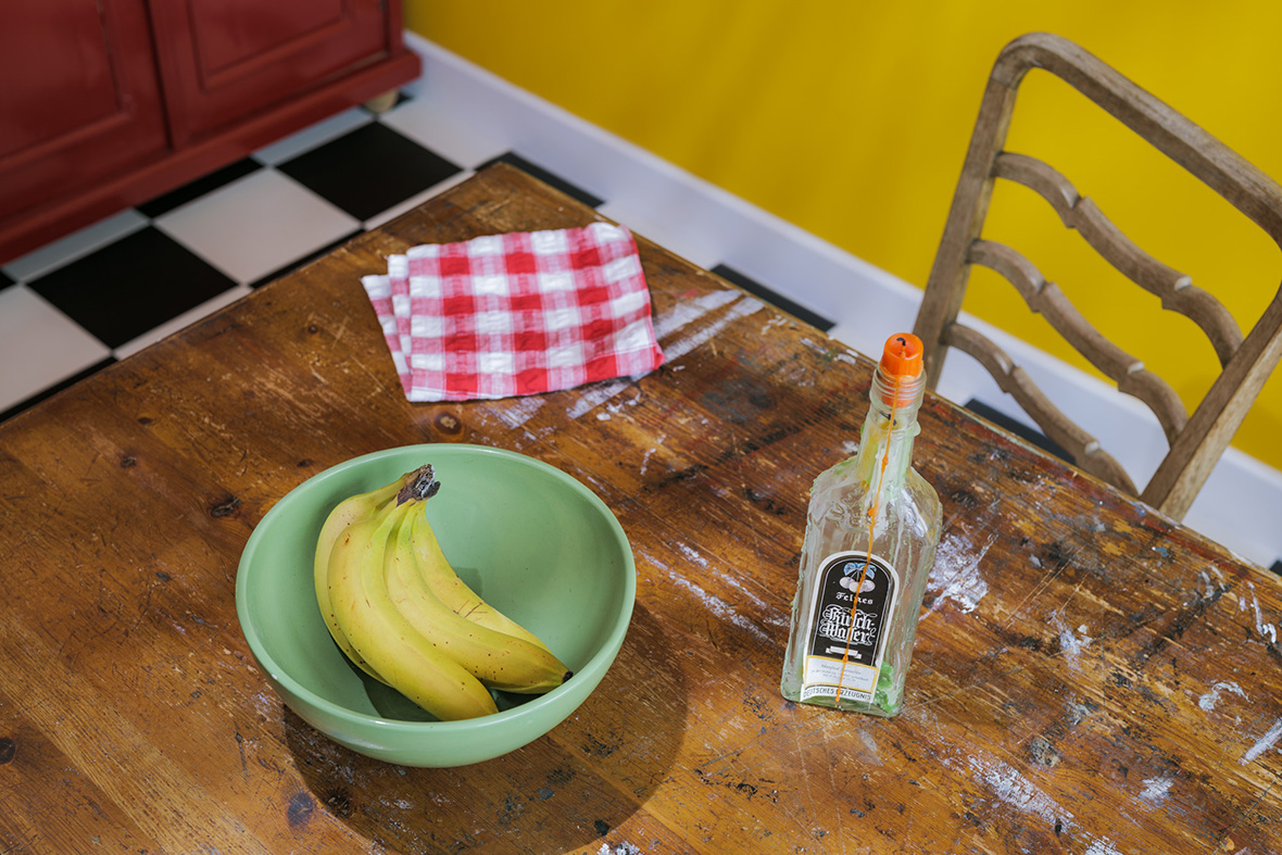 A still life looking down on a paint-smeared wooden table with a green bowl of yellow bananas with a red-chequered napkin behind and a candle in a bottle to the right of the bowl. A black and white chequered floor, yellow wall and bottom of a red cupboard are visible beyond the edges of the table. beyond