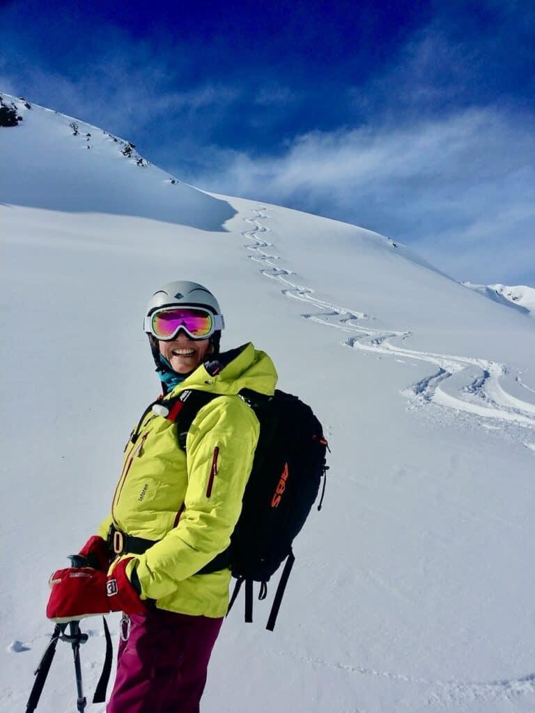 Skifahrerin mit gelber Jacke Abs Rucksack mit Spuren im Pulverschnee. Skitouren am Arlberg