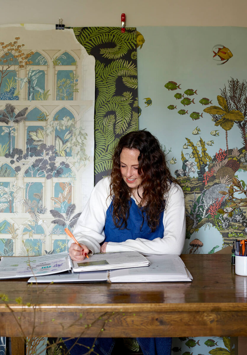 Josephine Munsey in her studio hand painting and drawing wallpaper designs
