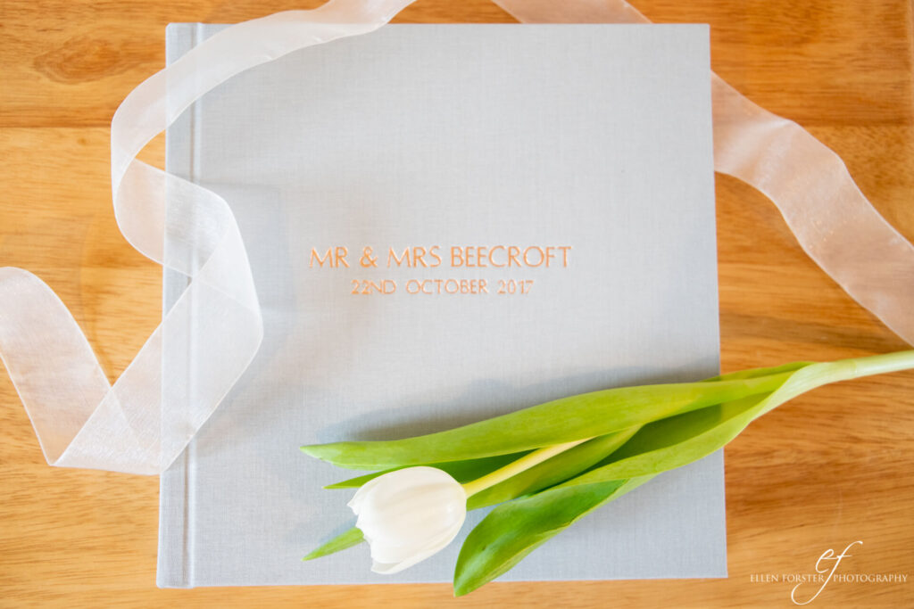 Flat lay of soft grey linen photo album, with white tulip resting on top.