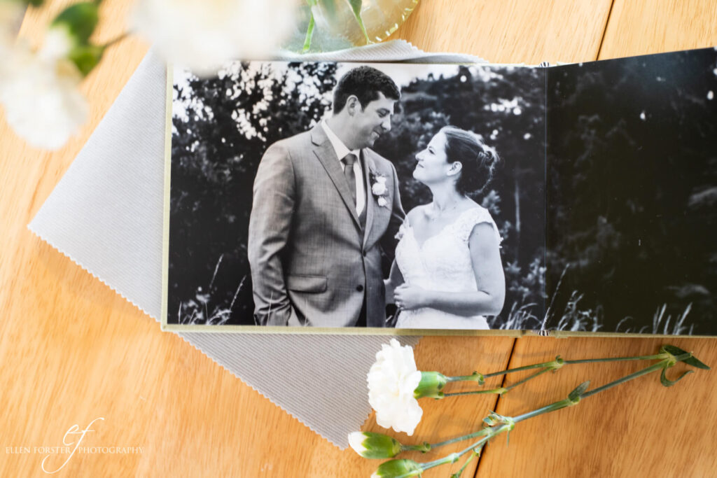 Black and white photo of Bride and Groom facing each other, on open page of wedding album.