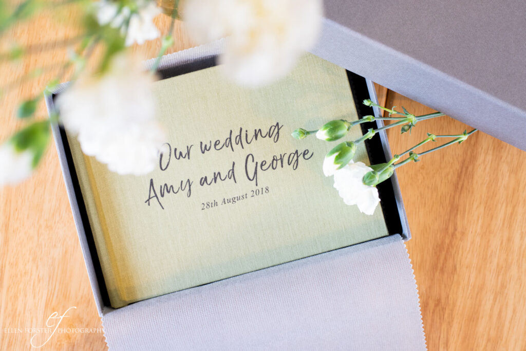"A5 wedding album in sage green linen cover with ""Our wedding"" and names and dates printed on the front."