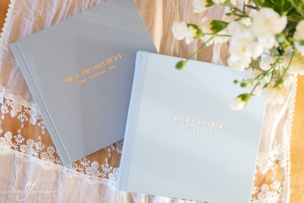 "10 x 10"" wedding albums in soft grey linen with rose gold embossed text, and pale blue leather with silver embossed text."
