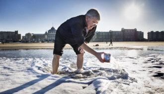 Den Haag , Scheveningen . Burgemeester van Zanen schept zeewater in een blik voor een alternatieve nieuwjaarsduik. Vanwege corona gaat de nieuwjaarsduik niet door. Mensen kunnen een blik toegestuurd krijg om thuis het water over het hoofd te gieten en zo het nieuwe jaar in te luiden. foto: Arie Kievit