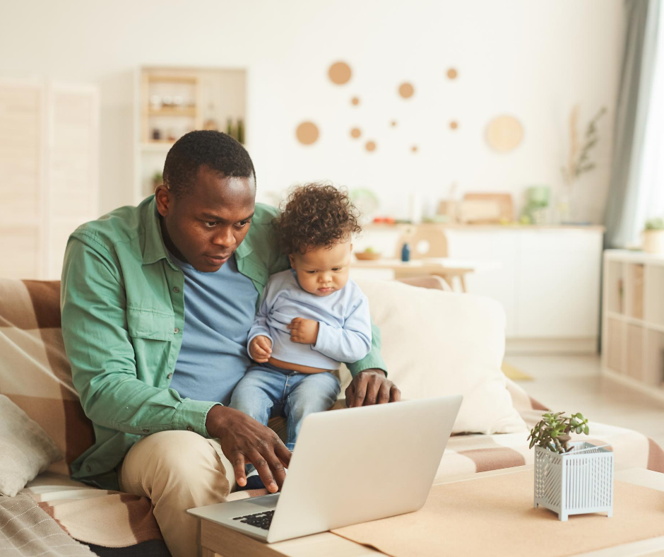 Father on laptop with baby on knee