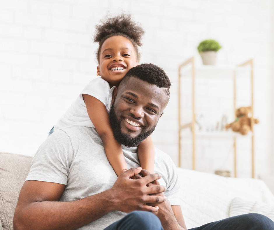 dad with daughter on his back at home, black African ethnicity