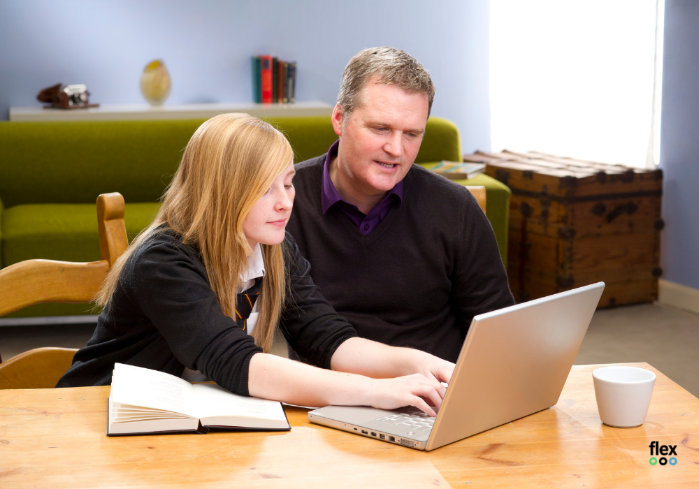 photo of dad with teenage daughter at a laptop