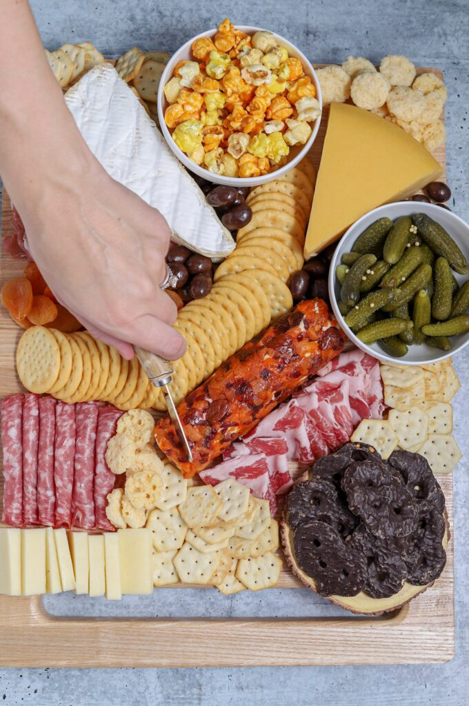 Charcuterie board with handing cutting. Crackers, cheese, chocolate, pickles, popcorn and deli meats