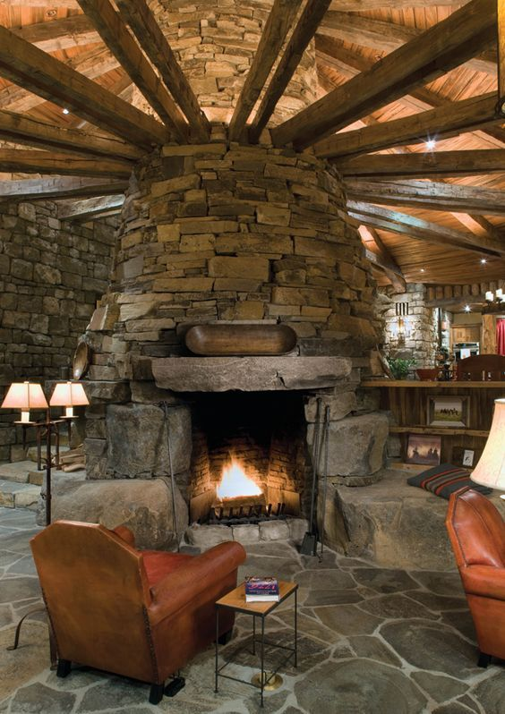 Mountain cabin with stone fireplace in the middle of the living room