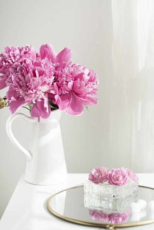Pink peony flower arrangement in white ceramic vase