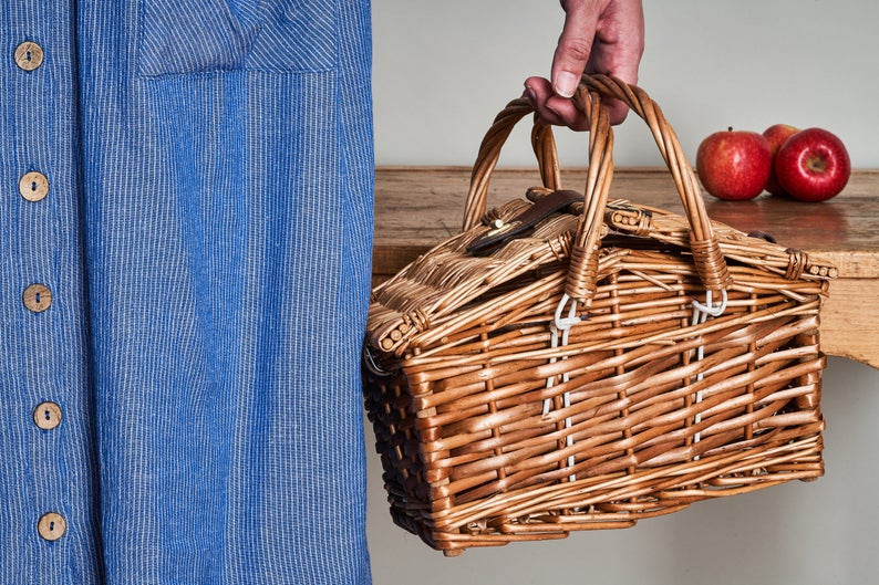 Small wicker basket picnic hamper with handles and lid