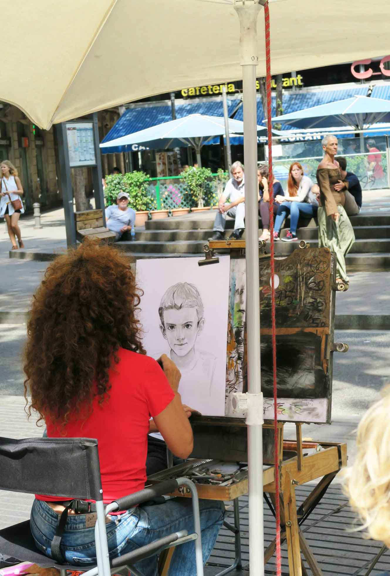 artist drawing a boy in Las Ramblas, Barcelona, Spain