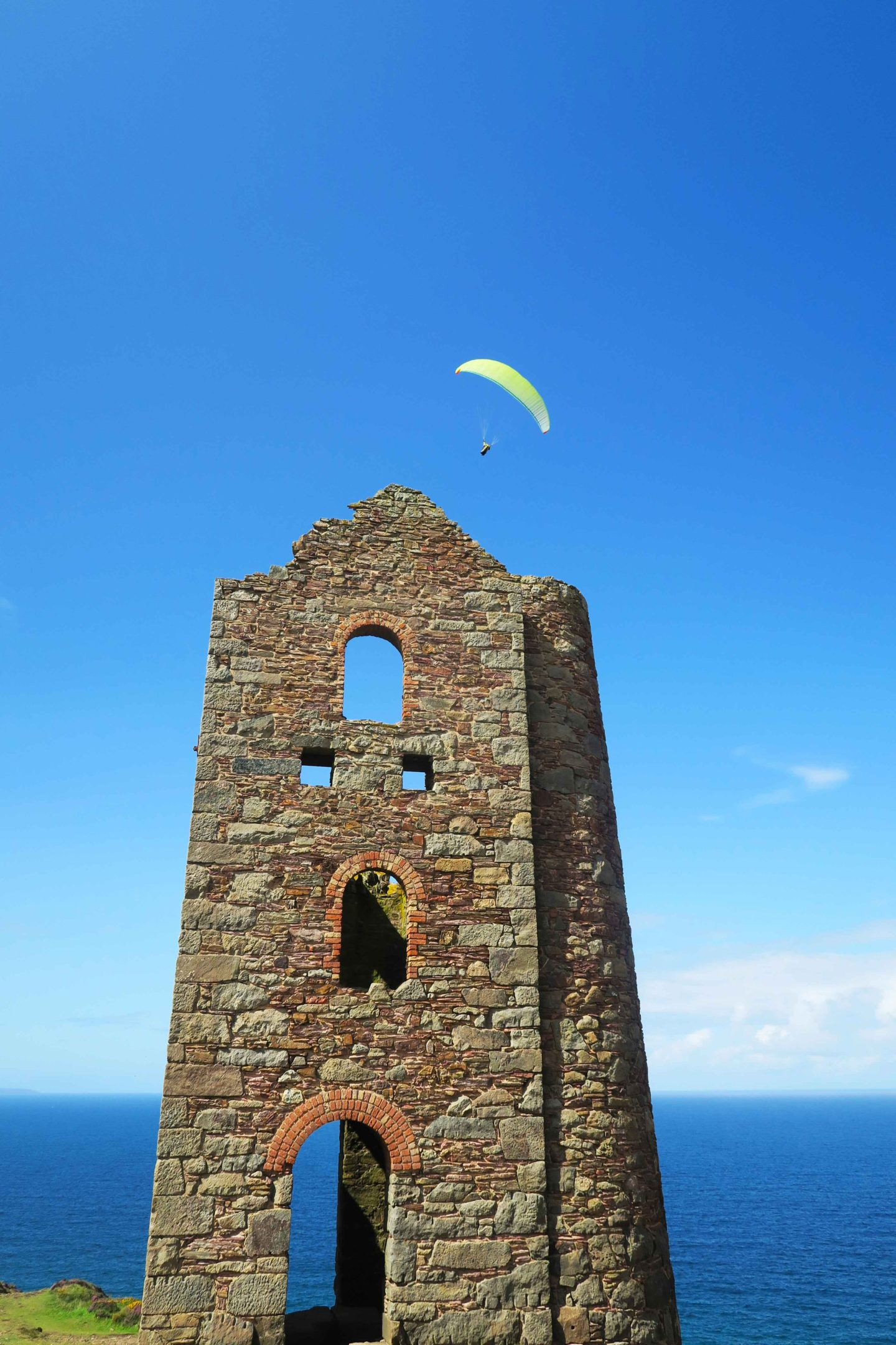 paraglider over national trust tin mine called wheal coates in cornwall