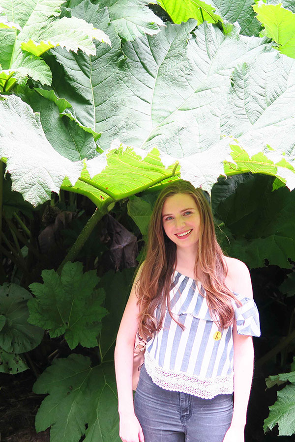 melissa carne standing under giant rhubarb at the lost gardens of heligan in cornwall