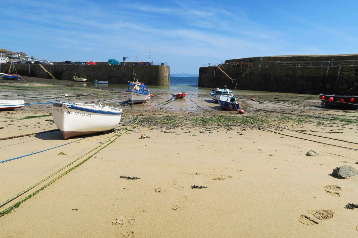tide out with fishing boats at mousehole harbour in cornwall