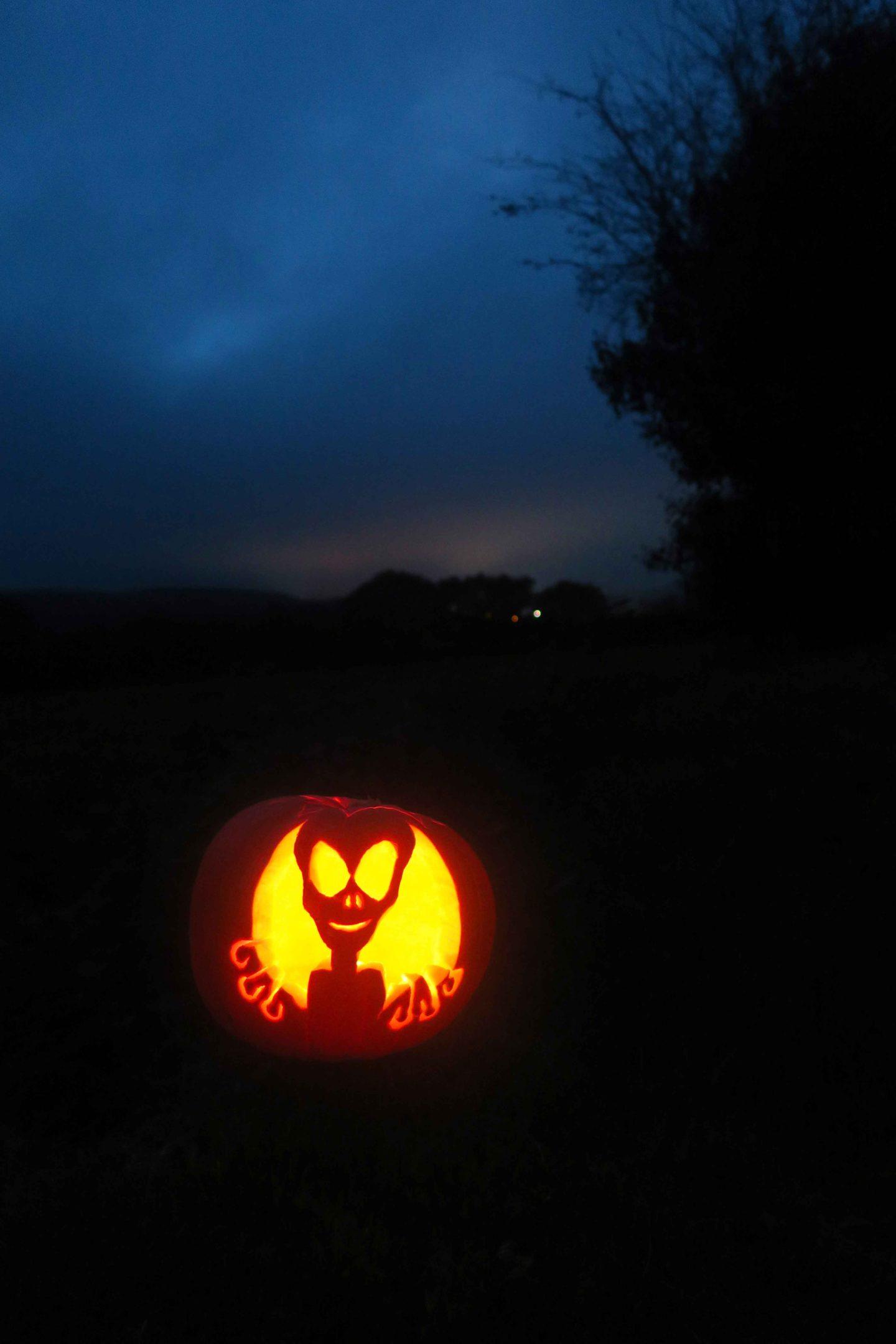alien pumpkin carving at night