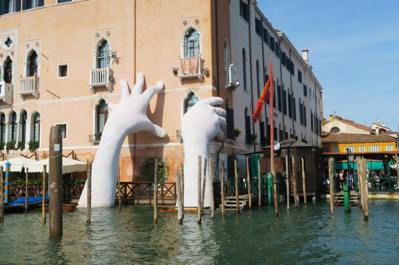 giant hand concrete statue on side of building in venice grand canal in italy