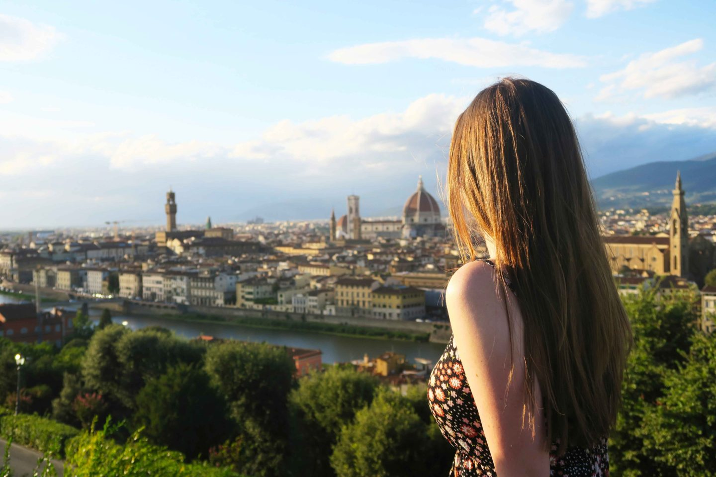 girl with brown hair looking our over the view of florence from piazzale michelangelo