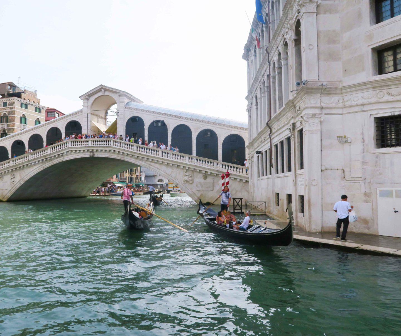 rialto bridge with godolas going underneath it in venice in italy