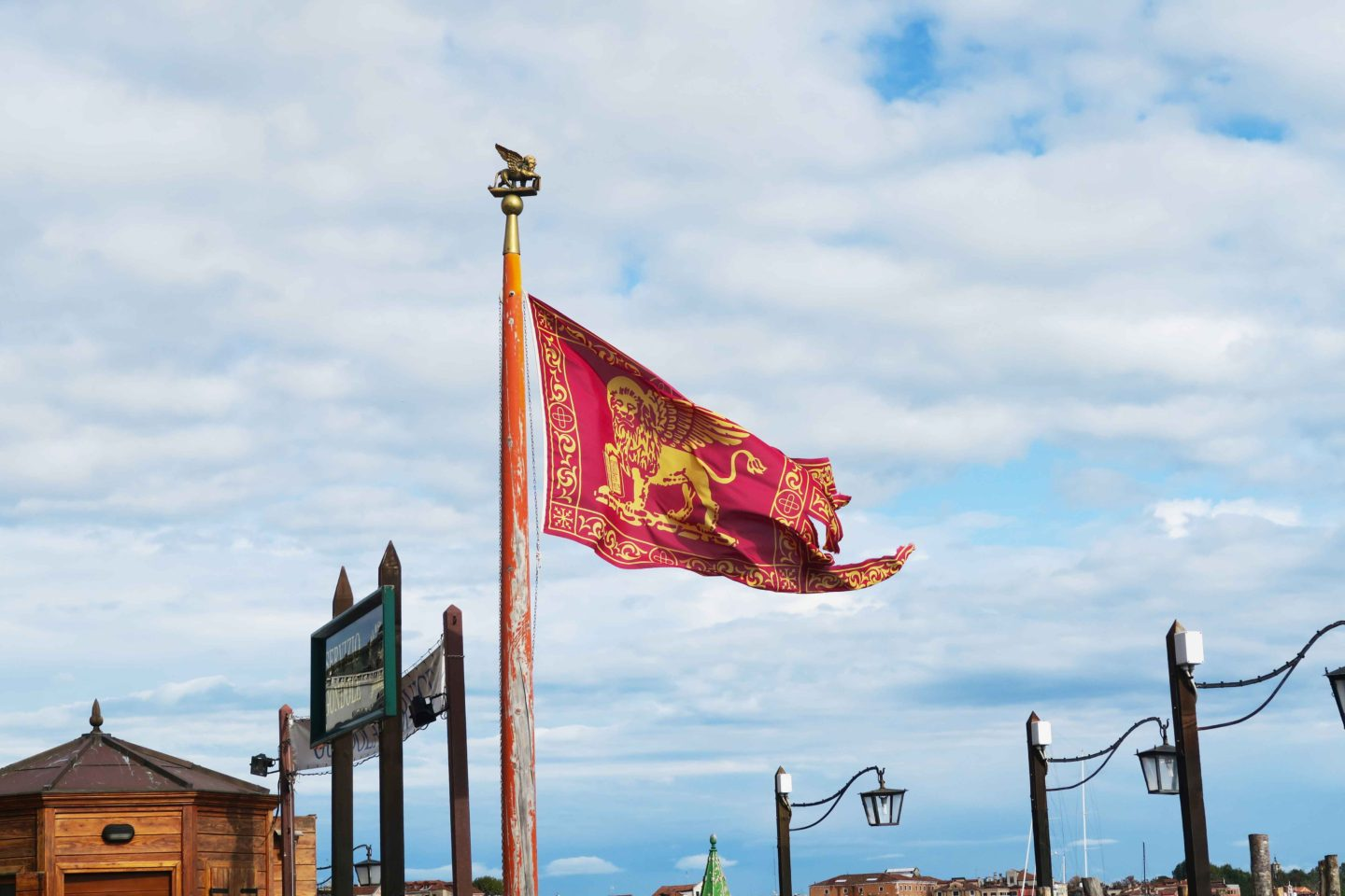 venetian flag red and gold lion flying in the sky in venice in italy