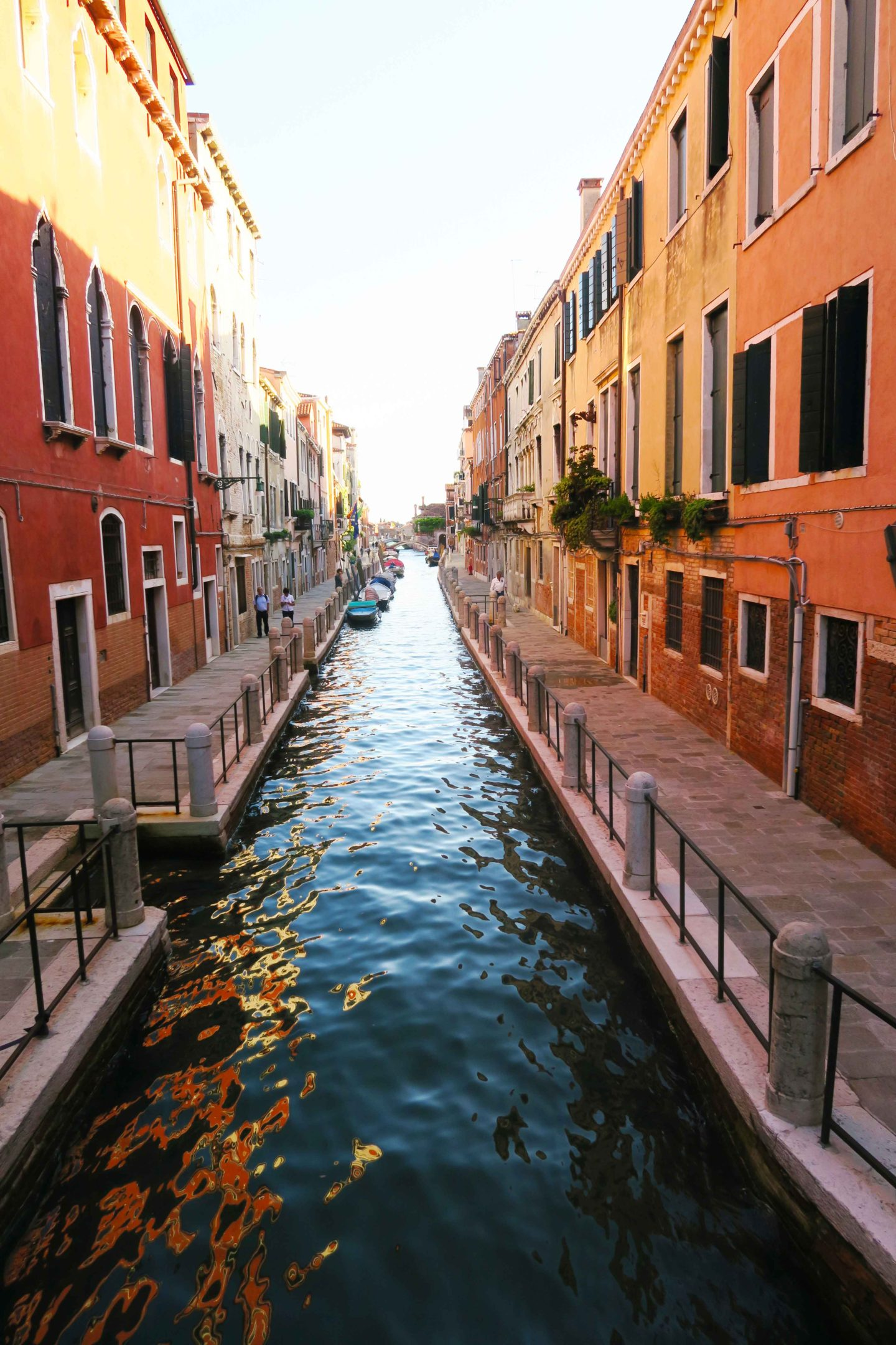 canal with orange houses either side in venice, italy