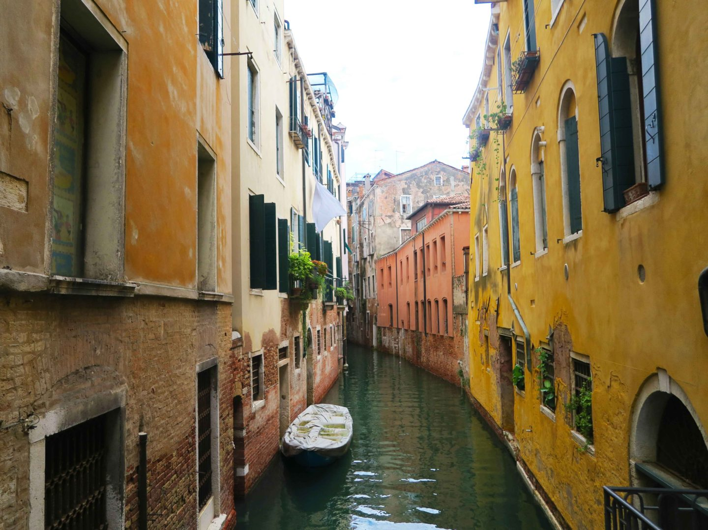 canal in venice with yellow houses