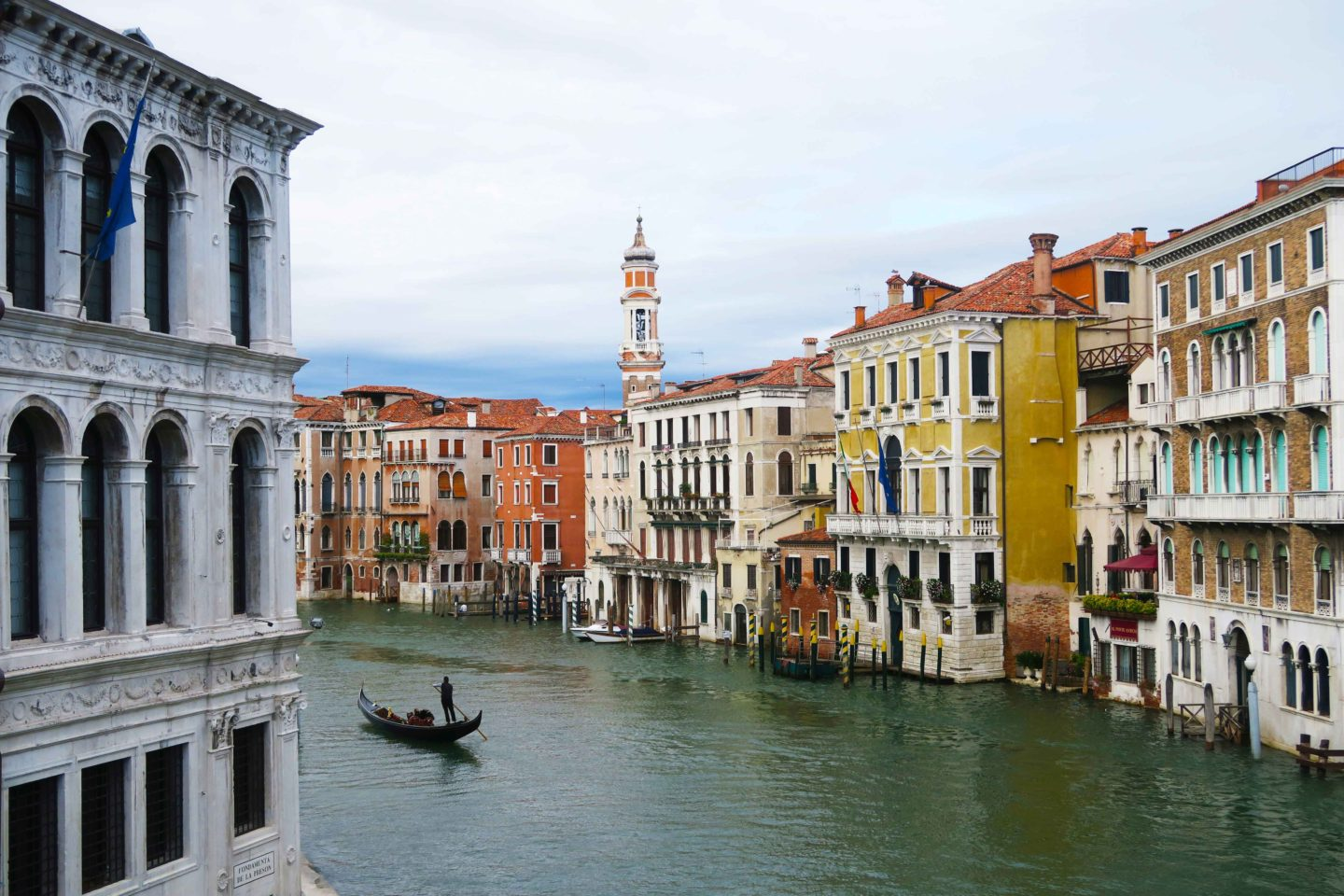 view from bridge in venice of a gondola in the canal