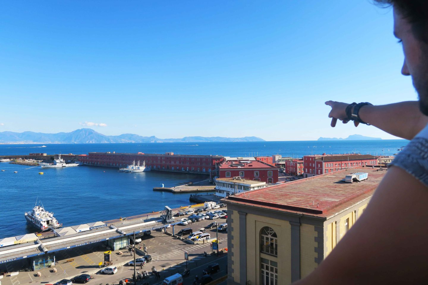 castel nuovo view with man point at the horizon in naples